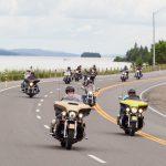 Motorcycle group on their way to New Liskeard. In the background the Presidents' Suites' Farr Island. / Groupe de moto en route vers New Liskeard. En arrière plan l'île Farr des Suites des Présidents.