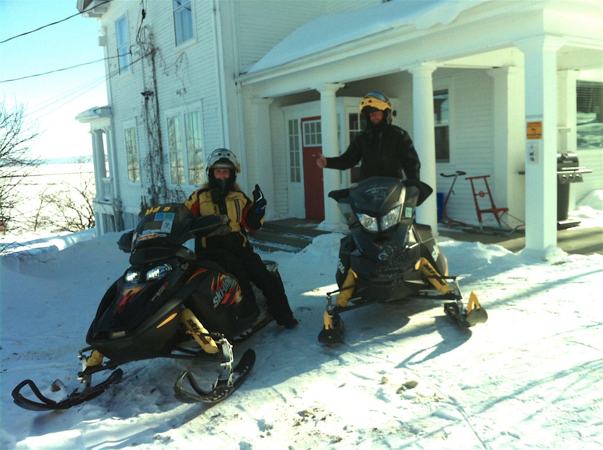 Snowmobile couple in front of the Presidents' Suites Villa. Several loops are possible from Haileybury. / Un couple en motoneige devant la Villa des Suites des Présidents. Plusieurs boucles sont possibles à partir de Temiskaming Shores.