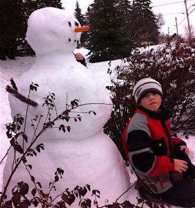 Snowman building at the Villa. Great family winter activity. / Construction d'un bonhomme de neige. Activité hivernale pour les familles.